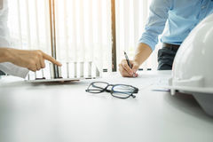 Architects engineer discussing at the table with blueprint - Closeup on hands and project print, Team group on construciton site royalty free stock image