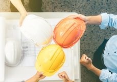 Architects and engineers took a helmet touching each other to sh royalty free stock image