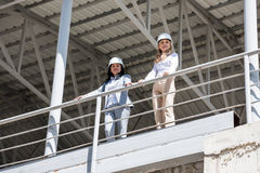 Architects in formal wear looking at camera while standing at construction site. Women architects in formal wear looking at camera while standing at construction Stock Photo