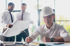 Architects in formal wear working at modern office, businessmen group Royalty Free Stock Images