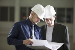 Architects Going Through File Folder In Warehouse Stock Photo