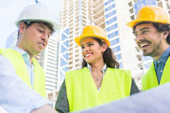 Architects with ground plot on construction site. Architects and civil engineers with ground plot on construction site of highrise building Royalty Free Stock Images