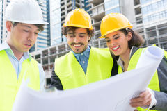Architects with ground plot on construction site Royalty Free Stock Images