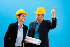 Architects in hardhat. Young architects in yellow hardhat against blue background Stock Photography