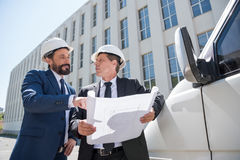 Architects in hardhats discussing blueprint while standing outdoors Stock Images