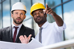 Architects in hardhats working with blueprint outside modern building Royalty Free Stock Image
