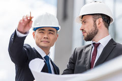 Architects in hardhats working with blueprint outside modern building Stock Image
