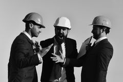 Architects hold clip folder. Men with beard and astonished faces. Have dispute. Managers wear smart suits, ties and hardhats on blue sky background. Building royalty free stock images