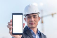 Architects holding a smartphone with isolated white screen.  stock photography