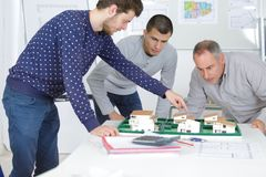 Architects with house model and blueprint working in office stock photos
