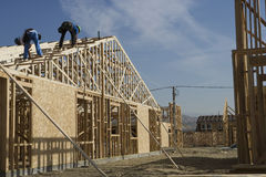 Architects Inspecting Rooftop Of New House. Architects inspecting rooftop at construction site Royalty Free Stock Photo