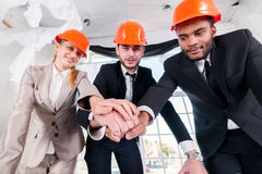 Architects laid hands on hands. Three businessmеn architect met Stock Images