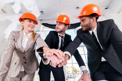 Architects laid hands on hands. Three businessmеn architect met Stock Photo