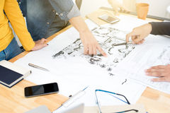 Architects or landscape designers discussing blueprints. Architects landscape designers discussing blueprints in the meeting Royalty Free Stock Photo