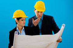 Architects looking blueprint. Young architects wearing hardhat looking at blueprint, isolated on blue Royalty Free Stock Photo