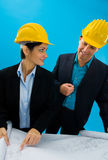 Architects looking blueprint. Young architects wearing hardhat looking at blueprint, isolated on blue Royalty Free Stock Photos