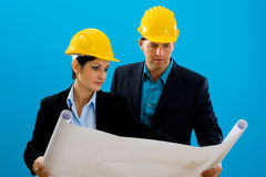 Architects looking blueprint. Young architects wearing hardhat looking at blueprint, isolated on blue Stock Image