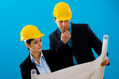 Architects looking blueprint. Young architects wearing hardhat looking at blueprint, isolated on blue Stock Photos