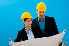 Architects looking blueprint. Young architects wearing hardhat looking at blueprint, isolated on blue Royalty Free Stock Images