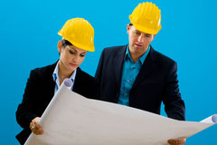 Architects looking blueprint. Young architects wearing hardhat looking at blueprint, isolated on blue Stock Images