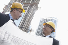 Architects looking at blueprint on construction site, Beijing Royalty Free Stock Image