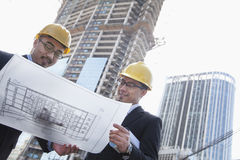 Architects looking at blueprint on construction site, Beijing Royalty Free Stock Photos