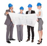 Architects looking at blueprint stock photography