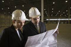 Architects Looking At Blueprint In Warehouse Stock Image