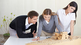 Architects looking at building. Three architects in office looking at 3D building model Royalty Free Stock Photography