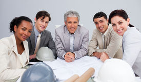 Architects in a meeting studying plans stock images