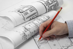 Architects planning on blueprint. Architect holding a red pencil. makes corrections to the blueprint royalty free stock image