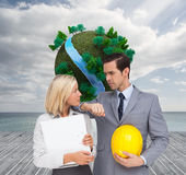 Architects with plans and hard hat looking at each other. Composite image of architects with plans and hard hat looking at each other Royalty Free Stock Photo