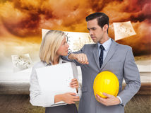 Architects with plans and hard hat looking at each other. Composite image of architects with plans and hard hat looking at each other Stock Photography