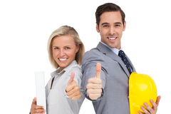 Architects with plans and hard hat showing thumbs up royalty free stock photos