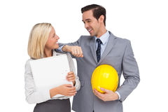 Architects with plans and hard hat smiling at each other. On white background Stock Photography