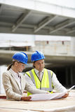 Architects Reading Blueprint At Site Stock Photography