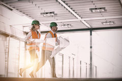 Architects running with blueprint Stock Photography