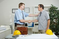 Architects shaking hands. Architects working at office - shaking hands, smiling royalty free stock image