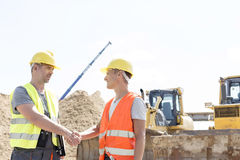 Architects shaking hands at construction site against clear sky Stock Photo