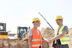 Architects shaking hands at construction site against clear sky Stock Photography