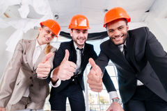 Architects show thumbs up. Three businessmеn architect met  Royalty Free Stock Photos