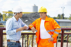 Architects standing against railing at construction site Royalty Free Stock Image