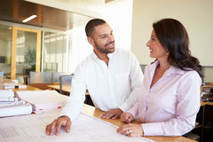 Architects Studying Plans In Modern Office Together Stock Photo
