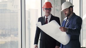 Architects talking with building plan in hands. Two architects discussing building plan standing near window stock video footage