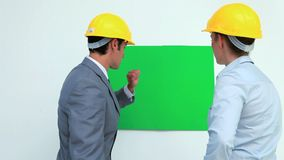 Architects talking in front of a blank space on the wall. While wearing safety helmet stock video footage