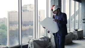 Architects talking standing near window. Two businessmen discussing building plan on paper while looking through the window stock video footage