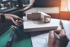 An architects thinking and designing mass model with shop drawing paper. On table stock photography