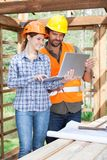 Architects Using Laptop Together At Construction Stock Photo