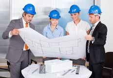Architects Wearing Blue Hardhat Looking At Blueprint Royalty Free Stock Photo