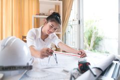 Architects who work on blueprints to work in-house architectural. Blueprints, rulers, calculators, laptops and compass. Engineering Tools Select Focus stock photo